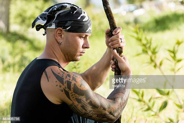 Characters: Tribal man with tattoos and piercings contemplates. Nature.