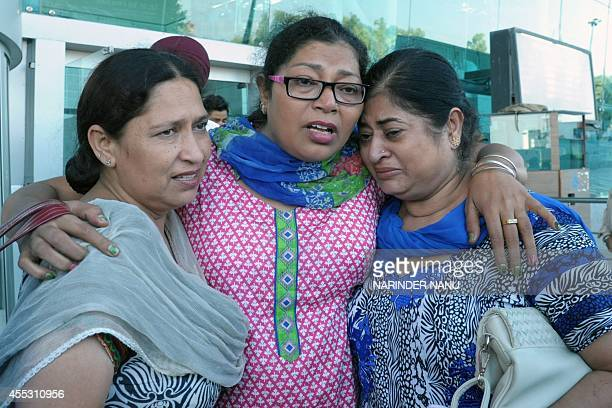 Charanjit Kaur an Indian Sikh evacuated from flooding in Srinagar hugs relatives following her arrival at the airport in Amritsar on September 12...