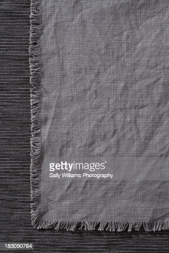 A charcoal grey napkin on a tablecloth