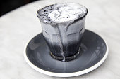 Charcoal super latte on marble background. Trendy healthy organic drink. Its melting