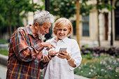 Senior couple using smartphones