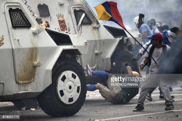 TOPSHOT A charging National Guard riot control vehicle knocks down a demonstrator during a protest against Venezuelan President Nicolas Maduro in...