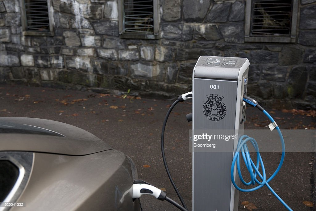 A charging plugs connects an electric vehicle (EV) to a charging station at Kongens gate near Akershus festning in Oslo, Norway, on Monday, Nov. 21, 2016. The International Energy Agency forecasts that global gasoline consumption has all but peaked as more efficient cars and the advent of electric vehicles from new players such as Tesla Motors Inc. halt demand growth in the next 25 years. Photographer: Fredrik Bjerknes/Bloomberg via Getty Images