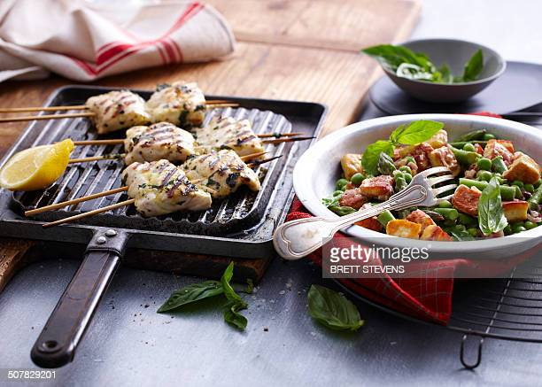 Chargrilled snapper skewers with lemon and bowl of salad