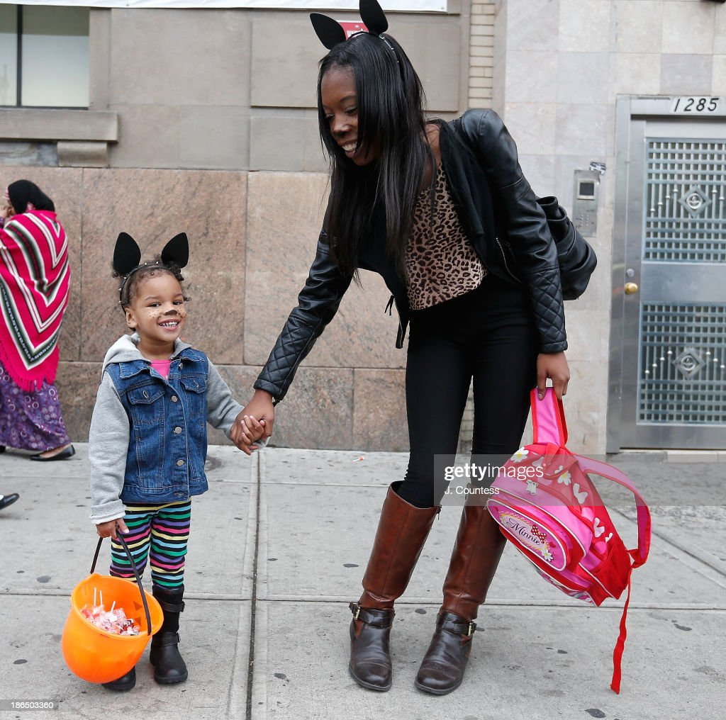 Charisma McKnight and her daughter pose for a photo in the heart of 'Bedstuy' as they 'Trick or Treat' in Brooklyn on October 31, 2013 in New York City.