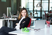 Charismatic Business Lady in official clothing black Jacket and white Shirt sitting at grey Table with Computer Glasses and Earphones in contemporary digital corporate Office with large Window on Back