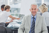 Charismatic businessman posing in the boardroom while colleagues are working behind