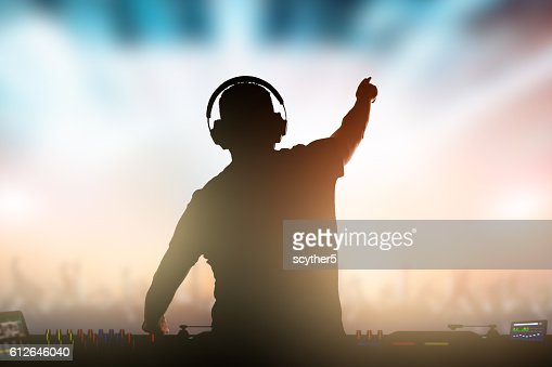 Charismatic disc jockey at the turntable. : Stock Photo