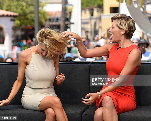 Charissa Thompson feels Charlotte McKinney's hair at 'Extra' at Universal Studios Hollywood on July 13 2015 in Universal City California