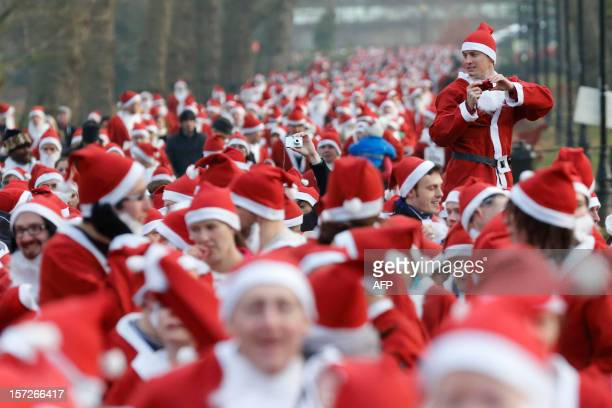 Charity runners dressed as Father Christmas participate in a 'Santa Run' charity fun run in Battersea Park in London on December 1 2012 Hundreds of...
