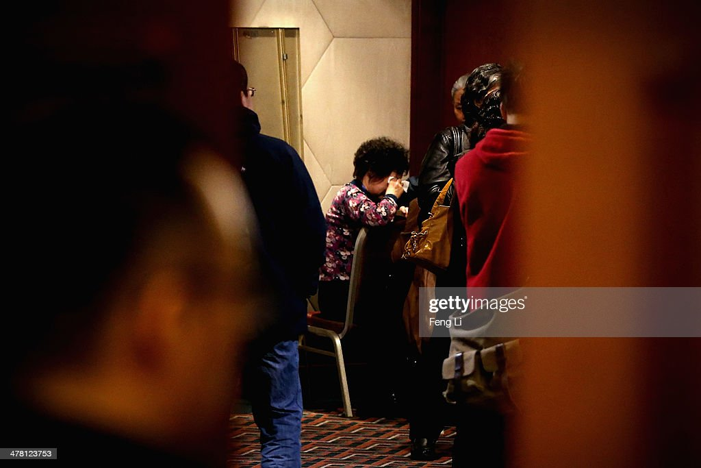 A charity worker comforts an emotional relative of a passenger onboard the Malaysia Airlines flight MH370 as families of the missing line up to receive a special condolence payment of 31,000 CNY (almost 5,000 USD) at Lido Hotel on March 12, 2014 in Beijing, China. Officials have expanded the search area for missing Malaysia Airlines flight MH370 beyond the intended flight path to include the west of Malaysia at the Straits of Malacca as new information surfaces about the time Subang air traffic control lost contact with the aircraft. The flight carrying 239 passengers from Kuala Lumpur to Thailand was reported missing on the morning of March 8 after the crew failed to check in as scheduled.