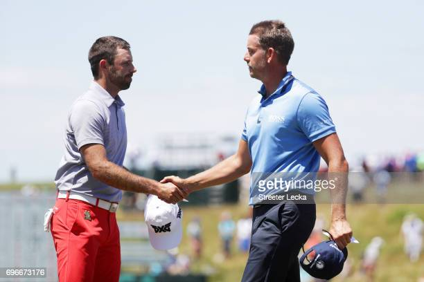 Charl Schwartzel of South Africa and Henrik Stenson of Sweden shake hands after finishing on the ninth green during the second round of the 2017 US...