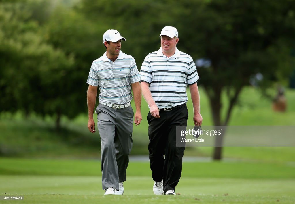 Charl Schwartzel of South Africa and Richard Finsh of England walk side by side as they compete during the final round of the Alfred Dunhill Championship at Leopard Creek Country Club on December 1, 2013 in Malelane, South Africa.