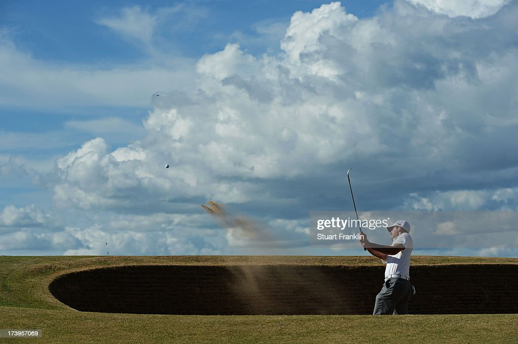Charl Schwartzel of South Africa hits a shot out of a bunker on the 12th hole during the first round of the 142nd Open Championship at Muirfield on July 18, 2013 in Gullane, Scotland.