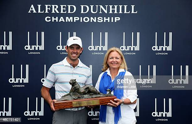 Charl Schwartzel of South Africa is presented the trophy by Gaynor Rupert wife of Johann Rupert CEO of Dunhill after winning the Alfred Dunhill...