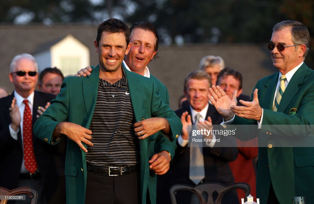 Charl Schwartzel of South Africa is presented with his Green Jacket by Phil Mickelson for winning the Masters after the final round of the 2011 Masters Tournament at Augusta National Golf Club on April 10, 2011 in Augusta, Georgia.