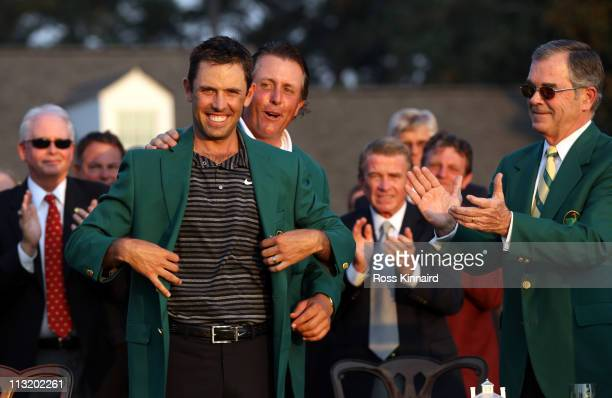 Charl Schwartzel of South Africa is presented with his Green Jacket by Phil Mickelson for winning the Masters after the final round of the 2011...