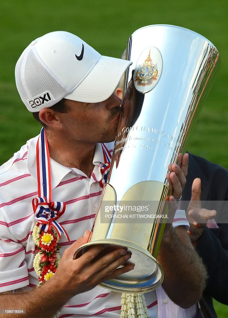 Charl Schwartzel of South Africa kisses the trophy after winning the Thailand Golf Championship at Amata Spring Country Club in Chonburi province on December 9, 2012. Schwartzel finished at 25 under-par total 263. AFP PHOTO / PORNCHAI KITTIWONGSAKUL