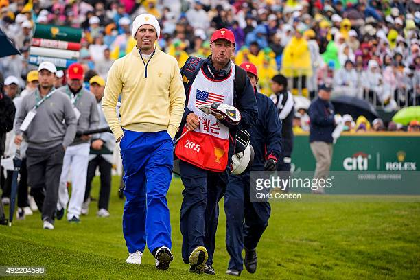 Charl Schwartzel of South Africa on the International Team walks off the first hole tee box with Jim 'Bones' Mackay of Team USA during the Sunday...