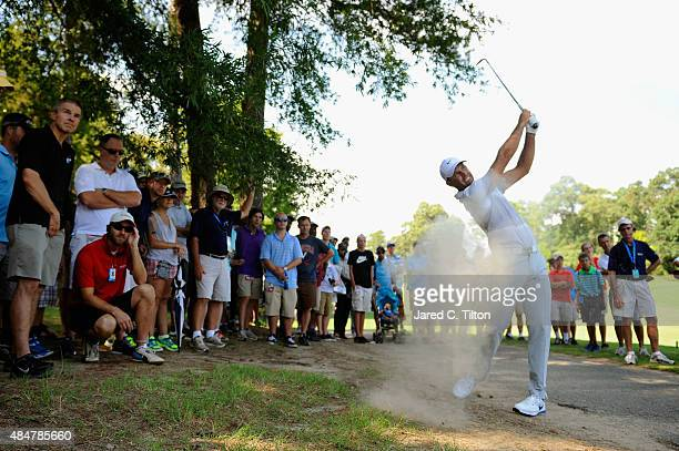 Charl Schwartzel of South Africa plays his second shot out of the dirt on the 11th hole during the second round of the Wyndham Championship at...