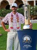 Charl Schwartzel of South Africa poses with the Thailand Golf Championship after winning the 2012 Thailand Golf Championship at Amata Spring Country...