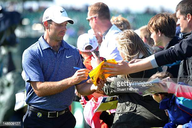 Charl Schwartzel of South Africa signs autographs for fans during the third practice round prior to the start of the 141st Open Championship at Royal...