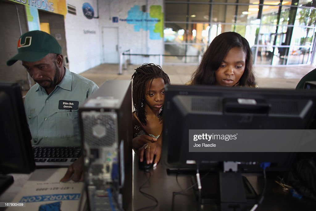 Charlene Crews (R) with her daugther, Joella Crews, uses a computer to fill out an application for a job during a job fair at the Miami Dolphins Sun Life stadium on May 2, 2013 in Miami, Florida. If voters approve a hotel tax hike to fund stadium renovations the jobs would be available. If not, the Dolphins management is indicating they would not be able to renovate the stadium nor create the jobs.