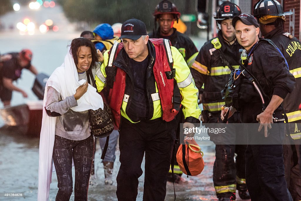 Charlene Stennis is escorted to safety after her son was rescued from a stranded vehicle in a flooded roadway October 4 2015 in Columbia South...