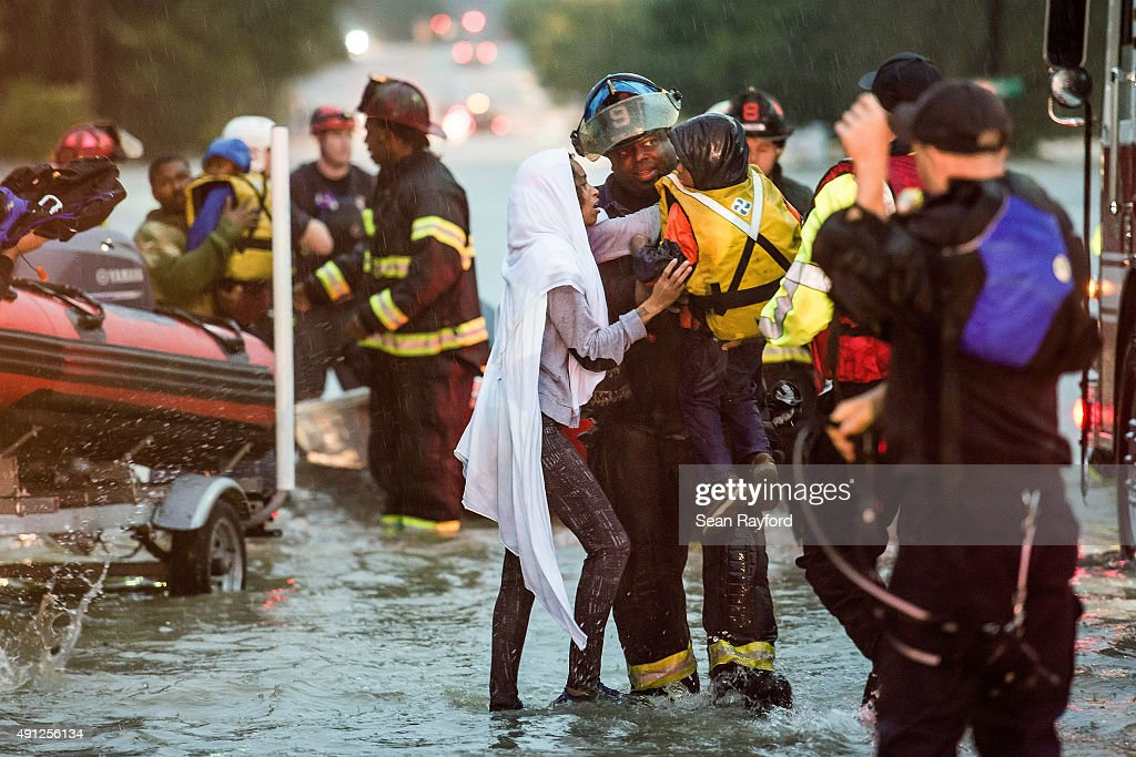 Charlene Stennis takes her son Christian HooFong from a fireman after being stranded in a vehicle by flood water October 4 2015 in Columbia South...