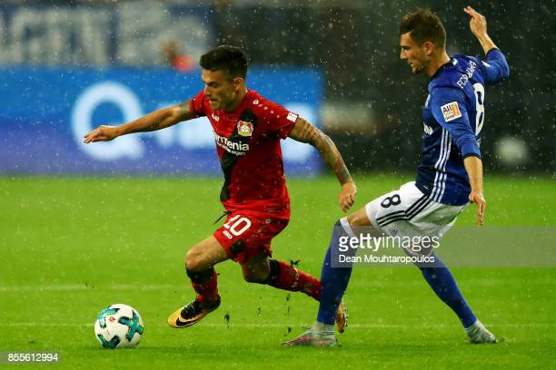 Charles Aranguiz of Bayer 04 Leverkusen is tackled by Leon Goretzka of Schalke 04 during the Bundesliga match between FC Schalke 04 and Bayer 04...