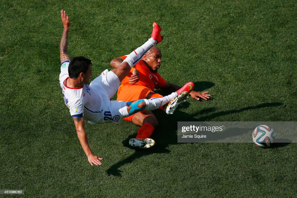 Charles Aranguiz of Chile and <a gi-track='captionPersonalityLinkClicked' href=/galleries/search?phrase=Nigel+de+Jong&family=editorial&specificpeople=579818 ng-click='$event.stopPropagation()'>Nigel de Jong</a> of the Netherlands collide during the 2014 FIFA World Cup Brazil Group B match between the Netherlands and Chile at Arena de Sao Paulo on June 23, 2014 in Sao Paulo, Brazil.