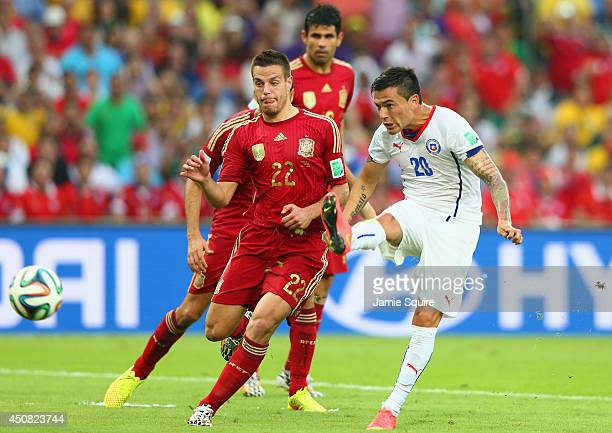 Charles Aranguiz of Chile shoots and scores his team's second goal against Cesar Azpilicueta of Spain during the 2014 FIFA World Cup Brazil Group B...