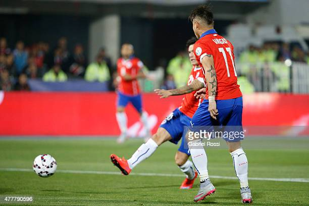 Charles Aranguiz of Chile shoots to score the opening goal during the 2015 Copa America Chile Group A match between Chile and Bolivia at Nacional...