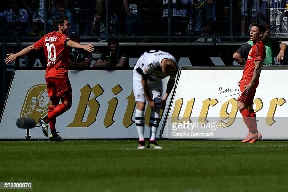 Charles Aranguiz of Leverkusen celebrates with team mate Hakan Calhanoglu after scoring the opening goal during the Bundesliga match between Borussia...