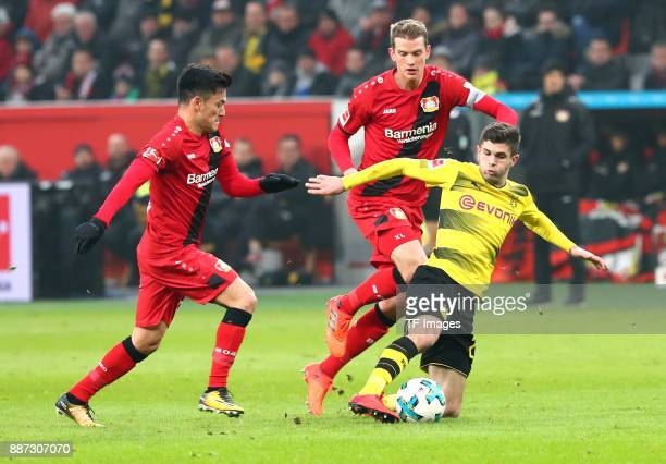 Charles Aranguiz of Leverkusen Lars Bender of Leverkusen and Christian Pulisic of Dortmund battle for the ball during the Bundesliga match between...