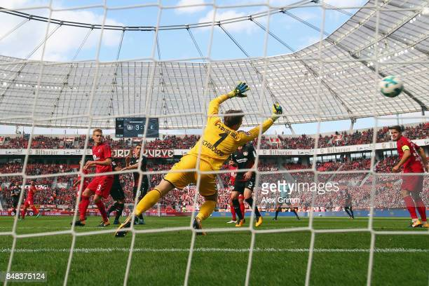 Charles Aranguiz of Leverkusen scores his team's second goal against goalkeeper Alexander Schwolow of Freiburg during the Bundesliga match between...