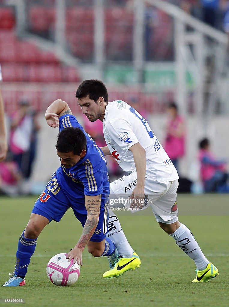 Charles Aranguiz of U de Chile fights for the ball with Cesar Fuentes during a match between O'Higgins and U de Chile as part of the Torneo Apertura at National Stadium, on October 05, 2013 in Santiago, Chile.