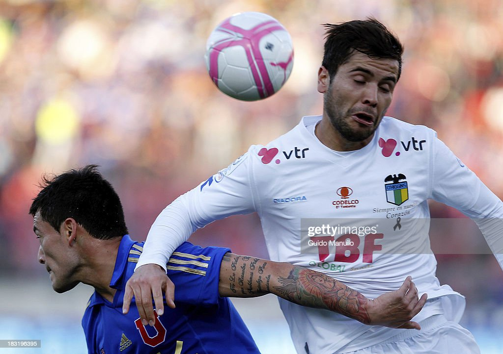 Charles Aranguiz of U de Chile fights for the ball with Claudio Meneses during a match between O'Higgins and U de Chile as part of the Torneo Apertura at National Stadium, on October 05, 2013 in Santiago, Chile.