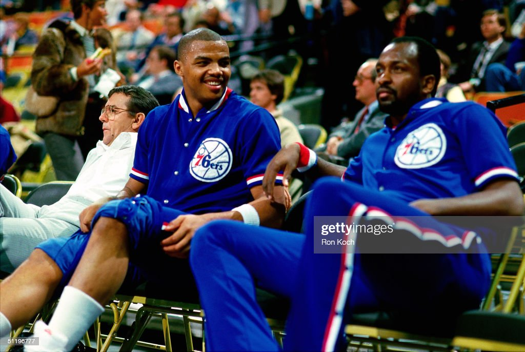 Charles Barkley of the Philadelphia 76ers shares a light moment with teammate Moses Malone while resting on the bench during an NBA game in 1985 at...