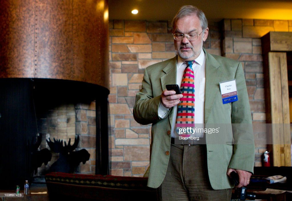 Charles Bean, deputy governor of the Bank of England, checks his mobile phone during the Federal Reserve Bank of Kansas City annual symposium near Jackson Hole, Wyoming, U.S., on Saturday, Aug. 28, 2010. Bean said more monetary stimulus may be required to sustain the recovery as the aftermath of the recession continues to hamper the economy. Photographer: Andrew Harrer/Bloomberg via Getty Images
