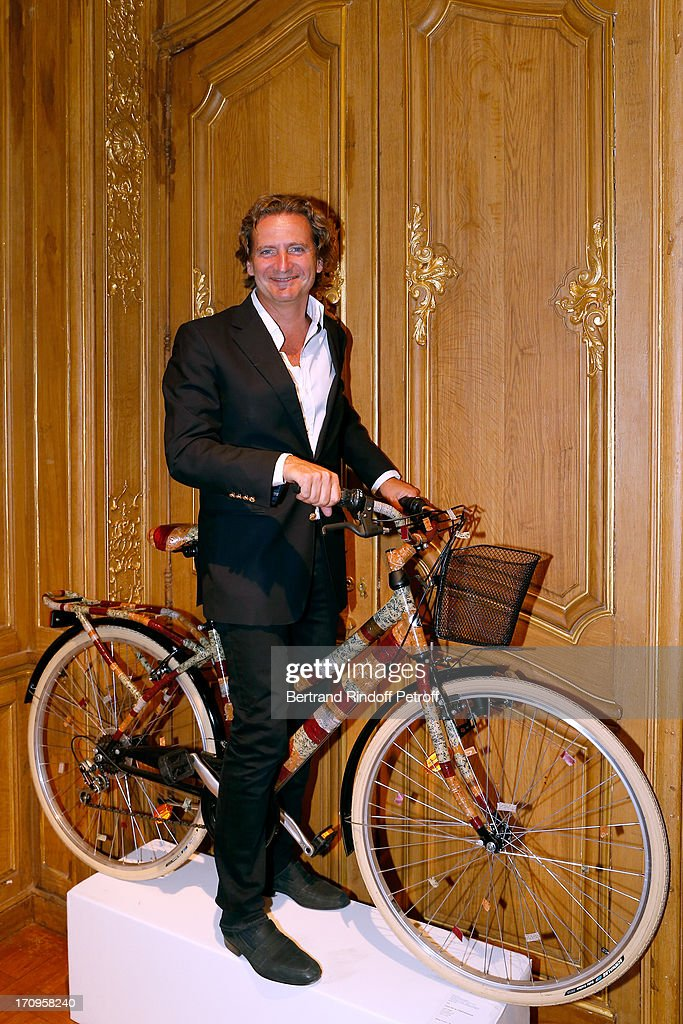 Charles Beigbeder standing on the bike from Ines de la Fressange at 'Arty Bike' Auction to benefit Association des Tout P'tits at Artcurial on June 20, 2013 in Paris, France.