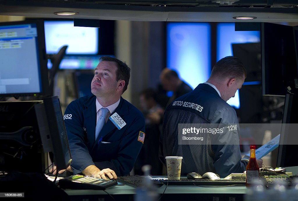 Charles Boeddinghaus, floor official with Getco Securities LLC, left, works on the floor of the New York Stock Exchange (NYSE) in New York, U.S., on Monday, Feb. 4, 2013. U.S. stocks fell, after the Standard & Poor's 500 Index jumped to a five-year high, on concern over increasing political tension in Europe as investors awaited data on factory orders. Photographer: Jin Lee/Bloomberg via Getty Images
