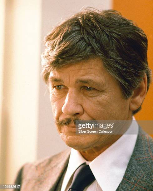 Charles Bronson US actor wearing a tweed jacket a white shirt and a black tie circa 1975