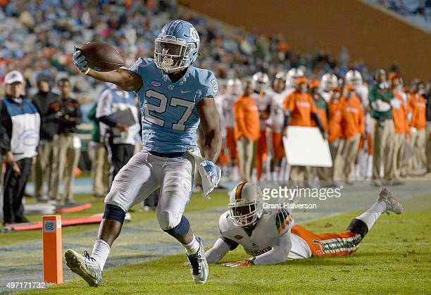 Charles Brunson of the North Carolina Tar Heels breaks away from Jermaine Grace of the Miami Hurricanes for a touchdown during their game at Kenan...