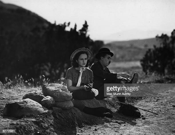 Charles Chaplin and Paulette Goddard sitting down in the countryside with Paulette looking depressed and Charlie adjusting his shoes Chaplin also...