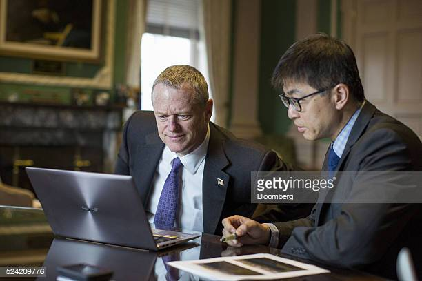 Charles 'Charlie' Baker governor of Massachusetts left views a laptop computer with a reporter during an interview at the Statehouse in Boston...
