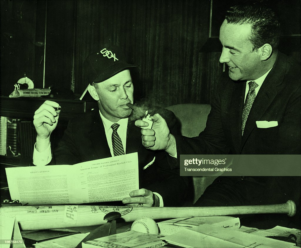 Charles Comiskey, Jr. lights up a cigar for Nellie Fox, who has just signed a new contract circa 1956 in Chicago, Illinois.