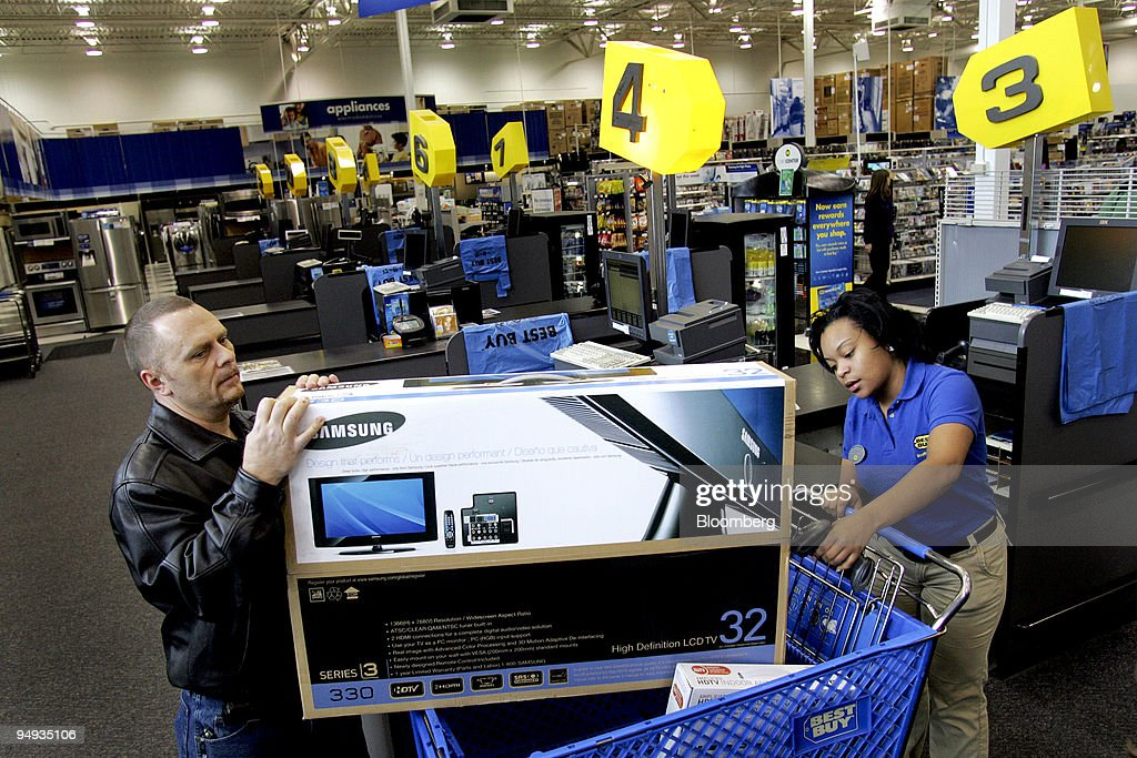 Charles Denofrio left purchases a flatpanel television as a Best Buy employee checks him out at a Best Buy store in Greensboro North Carolina US on...