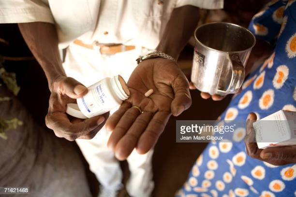 Charles Elegery and his partner Joyce Munduru show off their HIV medication from the ARV drug treatment at the MSF clinic on July 3 2006 in Arua...