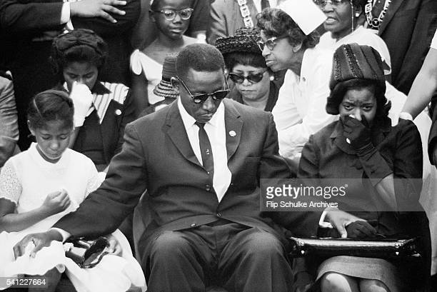 Charles Evers comforts his brother's wife and daughter at the funeral of slain civil rights leader Medgar Evers